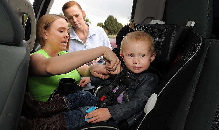 Air Force Staff Sgt. Ashley Sandoval (left), 21st Force Support Squadron, secures Savannah Butler (right) into her car seat as Savannah's mom, Air Force Staff Sgt. Montie Butler (center) looks on. Sandoval provided car seat training to Schriever Air Force Base, Colorado, parents at the Child Development Center in a program hosted by the 50th Space Wing safety office. (U.S. Air Force photo by Dennis Rogers)